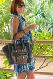 Fashion portrait of pretty young caucasian woman with handmade snakeskin python handbag. Sunny day on a tropical Bali Royalty Free Stock Photography