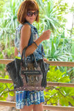 Fashion portrait of pretty young caucasian woman with handmade snakeskin python handbag. Sunny day on a tropical Bali Stock Image