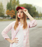 Fashion portrait pretty young girl wearing a shirt and red cap. Outdoors stock images