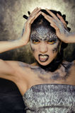 Fashion portrait of pretty young woman with creative make up like a snake. Close up Royalty Free Stock Image