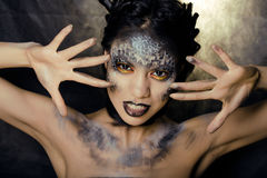 Fashion portrait of pretty young woman with creative make up like a snake. Close up Royalty Free Stock Images