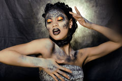Fashion portrait of pretty young woman with creative make up like a snake. Close up Stock Photography