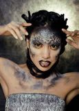 Fashion portrait of pretty young woman with creative make up like a snake. Close up Stock Image