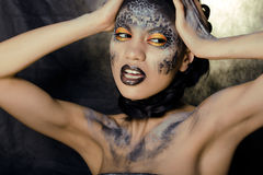 Fashion portrait of pretty young woman with creative make up like a snake Stock Photo