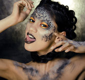 Fashion portrait of pretty young woman with creative make up like a snake. Close up Stock Images