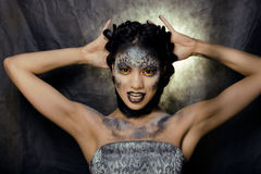Fashion portrait of pretty young woman with creative make up like a snake, halloween look Stock Photography
