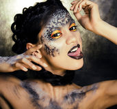 Fashion portrait of pretty young woman with creative make up like a snake, halloween look Royalty Free Stock Image