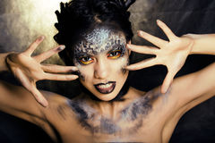 Fashion portrait of pretty young woman with creative make up like a snake, halloween look Royalty Free Stock Photos