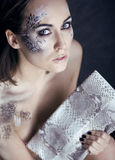 Fashion portrait of pretty young woman with creative make up like a snake. Fashion victim with python skin clutch Royalty Free Stock Photos