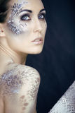 Fashion portrait of pretty young woman with creative make up like a snake. Fashion victim with python skin clutch Royalty Free Stock Image