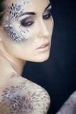 Fashion portrait of pretty young woman with creative make up like a snake. Fashion victim with python skin clutch Stock Images