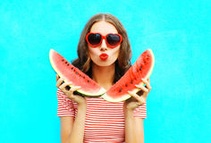 Fashion portrait pretty young woman is holding slice of watermelon and blowing lips. Over a colorful blue background royalty free stock photography