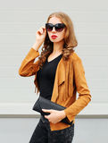 Fashion portrait pretty young woman wearing sunglasses jacket and black handbag clutch over grey Stock Image