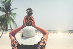 Fashion portrait rear of beautiful woman with fresh pineapple holds up - vacation on tropical beach in summer stock images