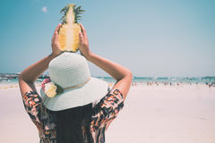 Fashion portrait rear of beautiful women with fresh pineapple holds up - vacation on tropical beach in summer. Royalty Free Stock Photography