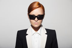 Fashion portrait of serious woman dressed as a secret agent. Or spy. Gray background royalty free stock image
