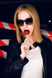 Fashion portrait of sexy blonde girl with candy in hand and red lips on the background of warning tape. Fashion portrait of sexy blonde girl with candy in hand Stock Image
