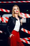 Fashion portrait of sexy blonde girl with red lips wearing a rock black style on the background of warning tape. Fashion portrait of sexy blonde girl with red Royalty Free Stock Image