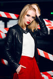 Fashion portrait of sexy blonde girl with red lips wearing a rock black style posing on the background of warning tape. Fashion portrait of sexy blonde girl Royalty Free Stock Image