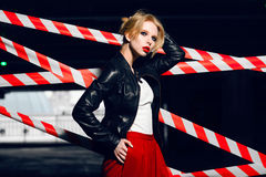 Fashion portrait of sexy blonde girl with red lips wearing a rock black style posing on the background of warning tape. Fashion portrait of sexy blonde girl Royalty Free Stock Images