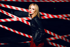 Fashion portrait of sexy blonde girl with red lips wearing a rock black style posing on the background of warning tape. Fashion portrait of sexy blonde girl Royalty Free Stock Photos