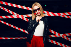 Fashion portrait of sexy girl with candy in hand wearing a rock style, sunglasses on the background of warning tape. Fashion portrait of sexy blonde girl with Royalty Free Stock Photo