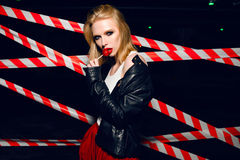 Fashion portrait of sexy girl with candy in hand wearing a rock style, sunglasses on the background of warning tape. Fashion portrait of sexy blonde girl with Stock Image