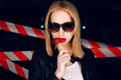 Fashion portrait of sexy girl with candy in hand wearing a rock style, sunglasses on the background of warning tape. Fashion portrait of sexy blonde girl with Stock Photography