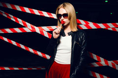 Fashion portrait of sexy girl with candy in hand wearing a rock style, sunglasses on the background of warning tape. Fashion portrait of sexy blonde girl with Stock Images