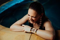 Fashion portrait of a girl in the pool. Turquoise water, black swimsuit and gold jewelry earrings. royalty free stock image