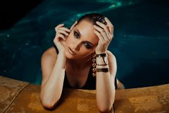 Fashion portrait of a sexy girl in the pool. Turquoise water, black swimsuit and gold jewelry earrings. Hands on pool edge Royalty Free Stock Photos
