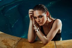Fashion portrait of a sexy girl in the pool. Turquoise water, black swimsuit and gold jewelry earrings. Hands on pool edge Royalty Free Stock Images