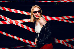 Fashion portrait of sexy girl wearing a rock black style and sunglasses posing on the background of warning tape. Fashion portrait of sexy blonde girl with red Royalty Free Stock Image