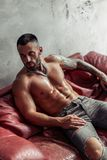 Fashion portrait of naked male model with tattoo and a black beard sitting in hot pose on red leather sofa. Loft room interio stock photo