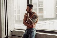 Fashion portrait of naked male model with tattoo and a black beard standing in hot pose on near the window. Loft room interio royalty free stock photo
