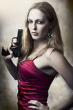 Fashion portrait of sexy woman holding gun Stock Photo