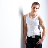 Fashion portrait of sexy young man. Fashion portrait of sexy young man in white shirt poses over wall with contrast shadows Stock Images