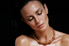 Fashion portrait of shining glamourous woman with wet skin on bl Royalty Free Stock Image