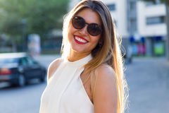 Fashion portrait of smiling cute young woman in the street. Stock Image