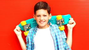 Fashion portrait smiling teenager boy with skateboard on red stock photography