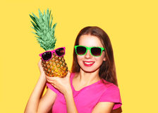 Fashion portrait smiling woman with pineapple in sunglasses over colorful yellow Stock Photography