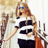 Fashion portrait of smiling young blonde woman with handbag wear Stock Photo