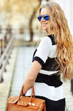 Fashion portrait of smiling young blonde woman with handbag wear Royalty Free Stock Photography
