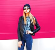 Fashion portrait stylish blonde woman in rock black style jacket, hat posing on city street over colorful pink wall stock images