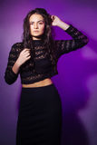 Fashion portrait of the stylish brunette on a violet background. Royalty Free Stock Photo