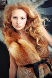 Fashion portrait stylish girl with curly hair. Fashion portrait stylish young girl with curly hair. Girl with foxy fur jacket Royalty Free Stock Image