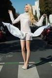 Fashion portrait of stylish  girl in white dress, Posing on the street background Royalty Free Stock Photo