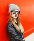 Fashion portrait stylish woman wearing a rock black leather jacket and sunglasses. With hat over red background royalty free stock image