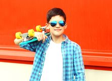 Fashion portrait teenager boy holds a skateboard in sunglasses. On red background royalty free stock images