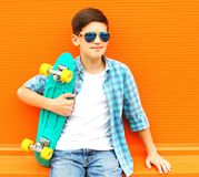 Fashion portrait teenager boy with skateboard wearing a sunglasses. On colorful orange background royalty free stock images